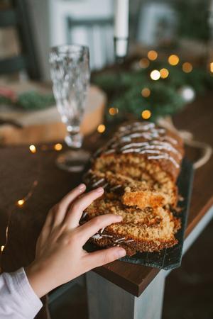Niña con torta celebrando la Navidad en la sala de cocina decorada Foto de archivo - 91982980