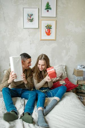 Junge kaukasische Paare verpackte Geschenke , die auf Bett zu Hause legen Standard-Bild - 95172967