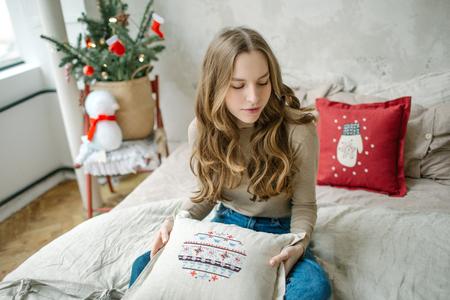 Junge schöne lockige Haare Brunettefrau in Jeans auf Bett im verzierten Raum Standard-Bild - 95189089