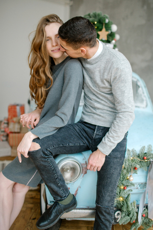 Young caucasian couple sitting on retro car in christmas decorated studio Archivio Fotografico - 95189090