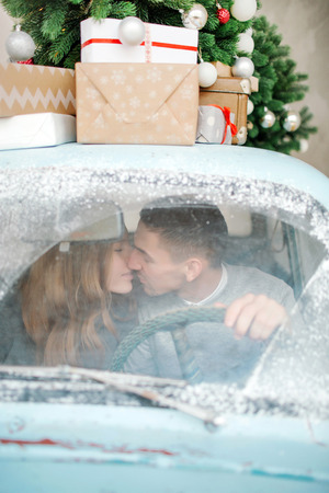 Young caucasian couple of male and female kissing in retro car in winter
