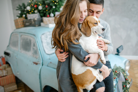 Young couple with beagle and retro car in christmas decorated studio Archivio Fotografico - 95176059