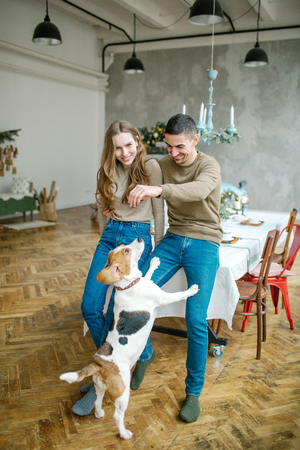 Young couple of caucasian male and female with beagle in dining room Archivio Fotografico - 95172996