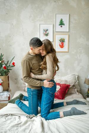 Junge kaukasischen Mann umarmt attraktive lockige Frau auf dem Bett Standard-Bild - 95176061