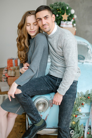 Young caucasian couple sitting on retro car in christmas decorated studio
