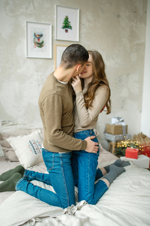 Young caucasian man hugging attractive curly woman on the bed Standard-Bild