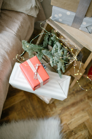 Christmas gifts in boxes on the floor with pine tree branch 스톡 콘텐츠