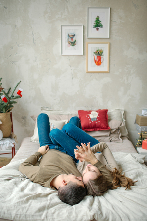 Young caucasian man hugging attractive curly woman on the bed Stockfoto