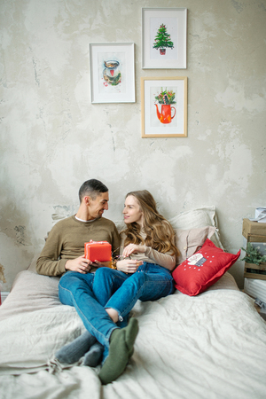 Young caucasian couple unboxing presents laying on bed at home Stok Fotoğraf