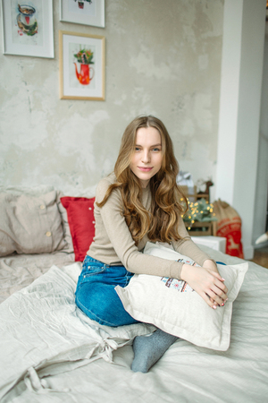 Young beautiful curly hair brunette woman in jeans on bed in decorated room Stok Fotoğraf
