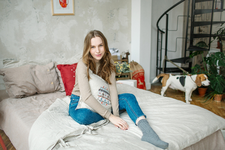 Young beautiful curly hair brunette woman with beagle in jeans on bed in decorated room Stok Fotoğraf