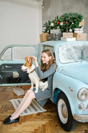 Young beautiful caucasian woman with beagle on lap sitting in retro car Stok Fotoğraf - 95189096