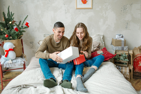 Young caucasian couple unboxing presents laying on bed at home Stockfoto