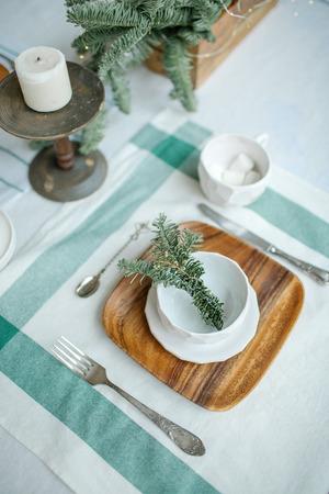 Leere Platte mit Zweig von Nadelbaum und Kerze auf dem Tisch Standard-Bild - 95200215