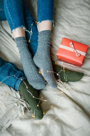 Mann , der Beine mit Frau auf dem Bett mit Geschenken in Kästen sich schlägt Standard-Bild - 95173005