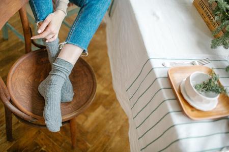 Frauenbeine in den Jeans auf dem Stuhl vor Speisetisch Standard-Bild - 95176067