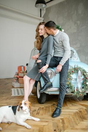 Junges Paar mit Beagle und Retro-Auto im Weihnachten dekoriert Studio Standard-Bild - 95200216