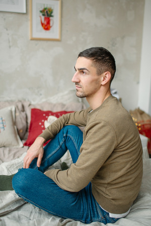 Young caucasian male alone sitting on the bed in apartment in jeans