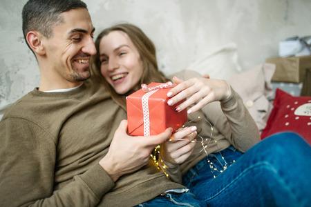 Junge kaukasische Paare verpackte Geschenke , die auf Bett zu Hause legen Standard-Bild - 95189100