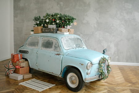 Blue retro car with christmas tree on the roof indoor 스톡 콘텐츠 - 95483636