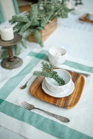 Empty plate with branch of coniferous tree and candle on table 스톡 콘텐츠