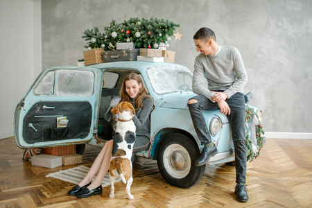 Young couple with beagle and retro car in christmas decorated studio