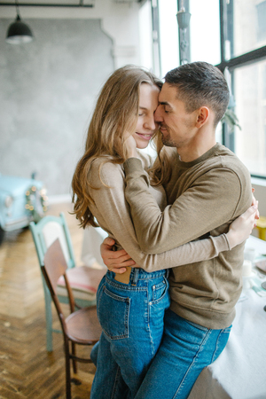 Young caucasian man hugging attractive curvy women in dining room Stockfoto