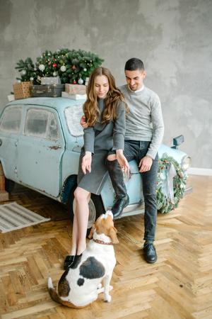 Junges Paar mit Beagle und Retro-Auto im Weihnachten dekoriert Studio Standard-Bild - 95176070