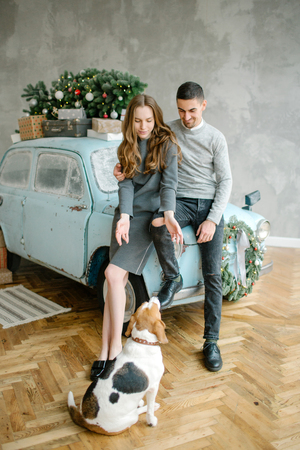 Young couple with beagle and retro car in christmas decorated studio Archivio Fotografico - 95176070