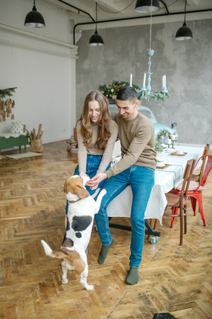 Young couple of caucasian male and female with beagle in dining room Foto de archivo - 95189103