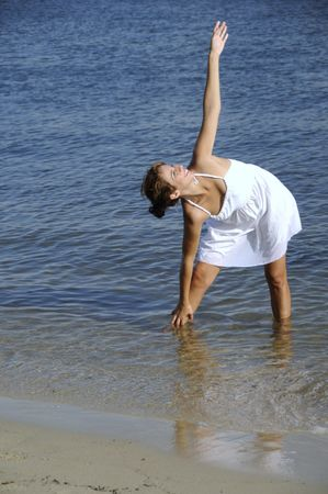 Woman in white stretching in the water at the beach Imagens