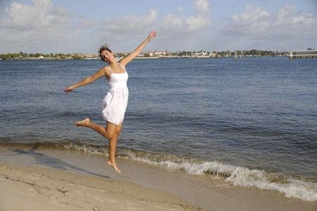 Woman in white dress jumping for joy at the beach