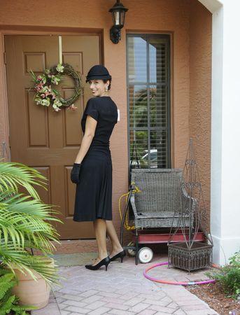 opening window: Hermosa mujer en sequined vestido negro con sombrero negro, guantes, entrar en su casa Foto de archivo