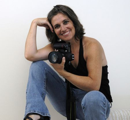 photo studio: Happy woman in black sleeveless top and blue jeans holding camera