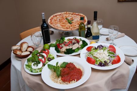beautiful table of italian salads, pasta, pizza and drinks photo