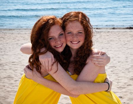 head in the sand: Twin Red-Headed teenage girls playing at the beach Stock Photo