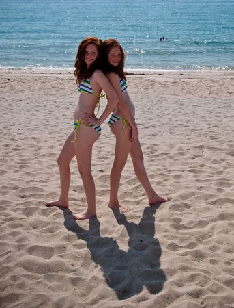 red head girl: Twin Red-Headed teenage girls playing at the beach Stock Photo