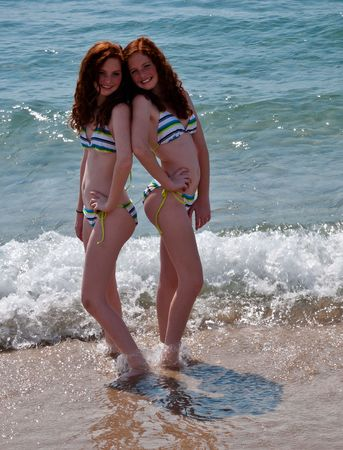 Twin Red-Headed teenage girls playing at the beach photo