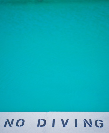 no diving sign: no diving sign at bottom of blue swimming pool Stock Photo