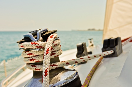 Red and white line wrapped around winch of sailboat photo