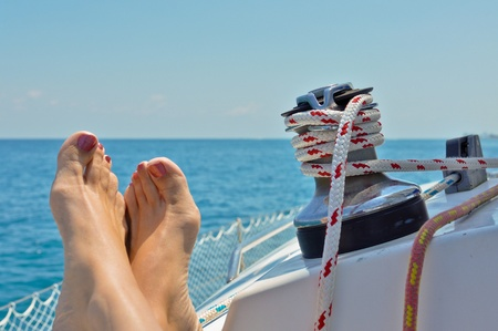 Woman with feet relaxing on a sailboat with lines in background photo