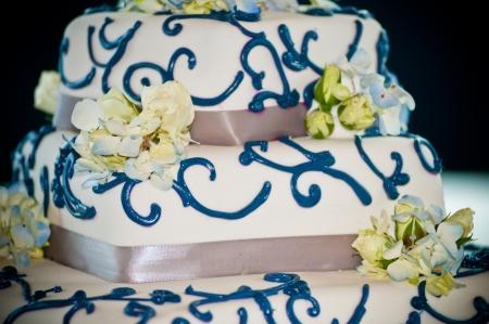 tiered: White wedding cake with blue swirls, decorated with blue hydrangeas Stock Photo