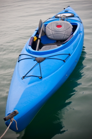 Blue kayak floating on calm water photo