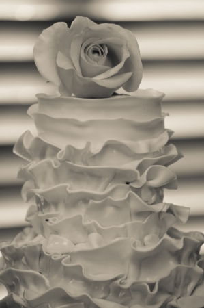 Black and white image of decorative wedding cake with single rose on top Stock Photo