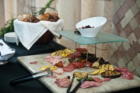carnes y verduras: Buffett tabla de placa de antipasti de carnes, verduras, quesos, panes Foto de archivo