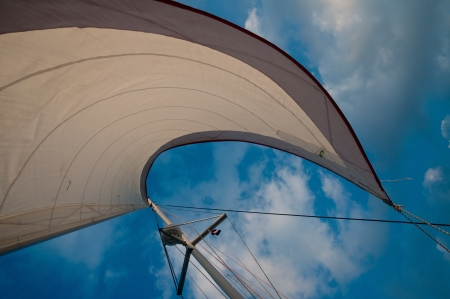 White sail set against blue sky and white clouds photo