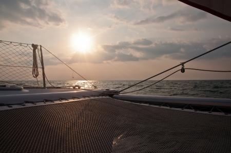 Sunset as seen from trampoline of a catamaran