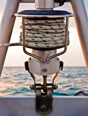 Green and white rope coiled around hardware of roller furling at the bow of a sailboat photo