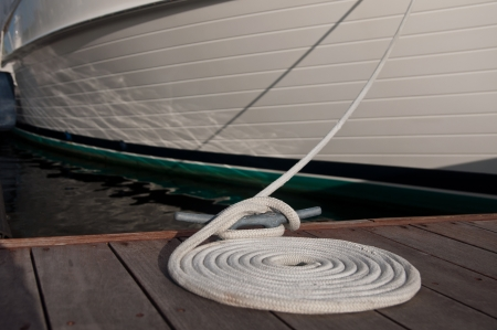 Dock cleat with a white line tied around it, then coiled beside the cleat.  boat secured to boat dock in background photo