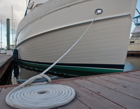 cleat: Dock cleat with a white line tied around it, then coiled beside the cleat.  boat secured to boat dock in background